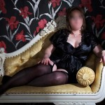 relaxing on chaise longue, in stockings and suspenders